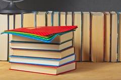 Mucchio dei libri su una superficie di legno Immagini Stock
