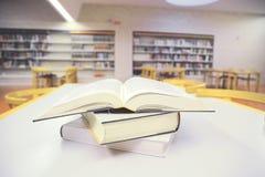 Mucchio dei libri su una tavola di legno in una biblioteca Fotografia Stock