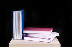 Mucchio dei libri variopinti su una priorità bassa nera Fotografia Stock