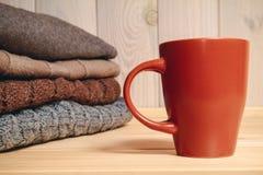Mucchio dei maglioni tricottati e di una tazza Fotografia Stock Libera da Diritti