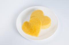 Mucchio dei pancake sotto forma di un cuore e di uno più sul piatto Fotografie Stock