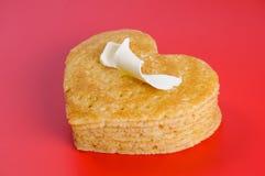 Mucchio dei pancake sotto forma di un cuore su rosso con il ricciolo di ma Fotografie Stock Libere da Diritti