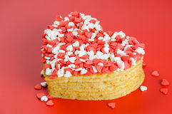 Mucchio dei pancake sotto forma di un cuore su rosso con poco briciolo Immagini Stock