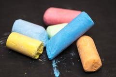 Mucchio dei pastelli dei colori differenti su una lavagna del fondo Fotografia Stock