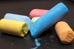 Mucchio dei pastelli dei colori differenti su una lavagna del fondo Fotografie Stock Libere da Diritti