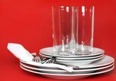 Mucchio dei piatti bianchi, vetri, forcelle, cucchiai. Fotografia Stock Libera da Diritti