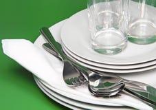 Mucchio dei piatti bianchi, vetri, forcelle, cucchiai. Fotografia Stock