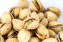 Mucchio dei pistacchi del sale isolato sulla fine bianca del fondo su immagini stock