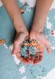 Mucchio dei puzzle nelle mani Immagini Stock