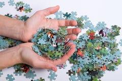 Mucchio dei puzzle nelle mani fotografia stock