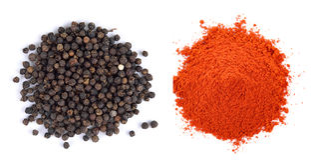 Mucchio dei semi della polvere rossa della paprica e del pepe nero su backg bianco Fotografia Stock Libera da Diritti