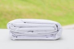 Mucchio dei tessuti bianchi piegati del panno sulla tavola di legno Fotografie Stock