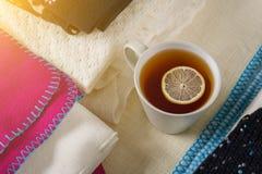 Mucchio dei vestiti di lana caldi sulla tavola, una tazza dell'immagine del fondo di inverno di tè caldo Immagini Stock