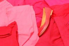 Mucchio dei vestiti rossi e rosa con le scarpe femminili Fotografia Stock