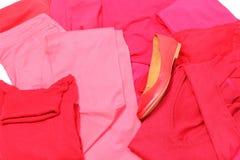 Mucchio dei vestiti rossi e rosa con le scarpe femminili Fotografie Stock