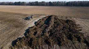 Mucchio del concime sul campo Lavoro del giacimento della molla Rilevamento aereo fotografie stock libere da diritti