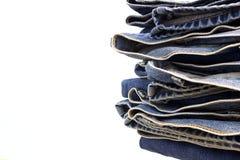 Mucchio del fondo di bianco dei jeans Immagini Stock