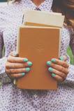 Mucchio del libro della tenuta della giovane donna in sue mani Immagine Stock