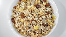 Mucchio del primo piano dell'alimento sano di muesli nella rotazione del piatto isolata alla vista superiore del fondo bianco archivi video