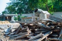 Mucchio del primo piano di legno inutile al cantiere con la betoniera vaga nel fondo immagine stock