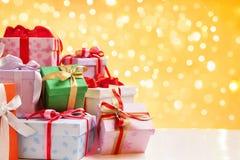 Mucchio del regalo di natale sopra l'indicatore luminoso della sfuocatura Fotografia Stock Libera da Diritti