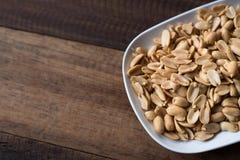 Mucchio dell'arachide fritta in un piatto sulla tavola di legno Fotografia Stock Libera da Diritti
