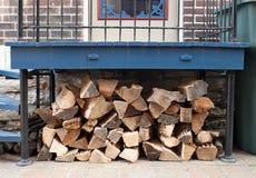 Mucchio della legna da ardere sotto la piattaforma del portico Fotografie Stock Libere da Diritti