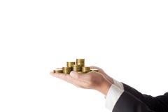 Mucchio della tenuta dell'uomo d'affari della mano delle monete immagini stock libere da diritti