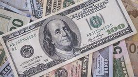 Mucchio delle banconote differenti del dollaro di denominazioni con il fuoco su cento banconote in dollari sulla cima Immagini Stock