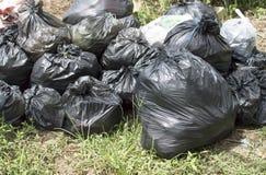 Mucchio delle borse di immondizia di plastica nere sulla terra Immagine Stock