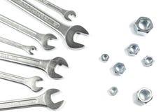 Mucchio delle chiavi delle dimensioni differenti contro i dadi delle dimensioni differenti isolati su bianco Fotografia Stock Libera da Diritti
