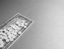 Mucchio delle compresse su cento banconote in dollari fotografie stock