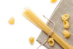 Mucchio delle coperture e degli spaghetti crudi dei maccheroni su insaccamento marrone, selec fotografia stock libera da diritti