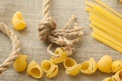 Mucchio delle coperture e degli spaghetti crudi dei maccheroni sull'insaccamento organico immagine stock libera da diritti