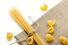 Mucchio delle coperture e degli spaghetti dei maccheroni con la corda su insaccamento marrone fotografia stock libera da diritti