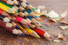 Mucchio delle matite colorate con i trucioli, fondo di legno, vista superiore Fotografia Stock