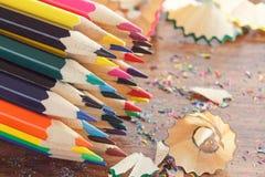 Mucchio delle matite colorate con i trucioli, fondo di legno, vista superiore Fotografie Stock