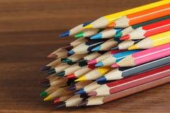 Mucchio delle matite colorate, fondo di legno Immagine Stock