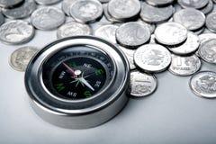 Mucchio delle monete con la bussola Fotografia Stock
