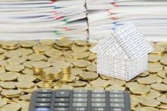 Mucchio delle monete di oro con la casa sulle monete di oro della pila Immagini Stock Libere da Diritti