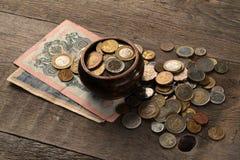 Mucchio delle monete e delle banconote su una tavola di legno Fotografia Stock Libera da Diritti