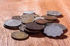 Mucchio delle monete su fondo di legno (fuoco selettivo usato) Fotografie Stock Libere da Diritti