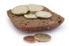Mucchio delle monete su una fetta di pane. Fotografie Stock