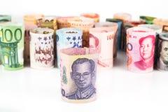 Mucchio delle note acciambellate di valuta con la baht della Tailandia nella parte anteriore Fotografie Stock Libere da Diritti