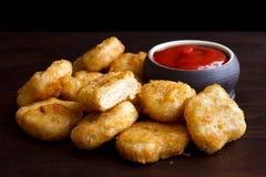 Mucchio delle pepite di pollo avariate fritte in grasso bollente dorate con ru vuoto fotografia stock