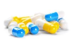 Mucchio delle pillole gialle mediche e delle pillole blu Immagine Stock
