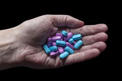 Mucchio delle pillole in palma orizzontale da sopra sul nero Immagine Stock