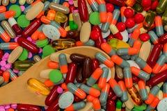 Mucchio delle pillole variopinte e del cucchiaio di legno Medicina, vitamine, supplemento e minerali Farmacoresistenza degli anti Fotografia Stock Libera da Diritti