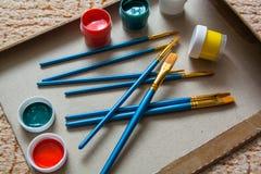 Mucchio delle spazzole di arte e di pochi barattoli di pittura Fotografie Stock