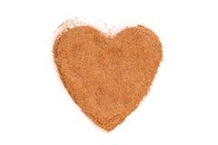 Mucchio di cannella a terra isolato nella figura del cuore Immagini Stock
